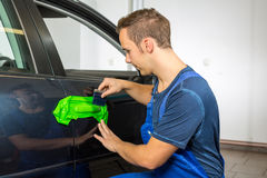 Car wrapping specialist wraps car door handle with adhesive foil or film. Car wrapping specialist wraps a car door handle with adhesive foil or film Royalty Free Stock Images