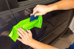 Car wrapping specialist wraps car door handle with adhesive foil or film. Car wrapping specialist wraps a car door handle with adhesive foil or film royalty free stock photo