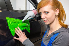 Car wrapping specialist wraps car door handle with adhesive foil or film. Car wrapping specialist wraps a car door handle with adhesive foil or film Royalty Free Stock Photography
