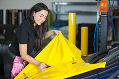 Car wrapping specialists straightening vinyl foil or film. To remove ari bubbles stock image