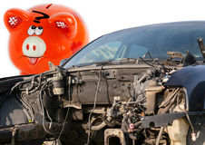 Car wreck and orange piggy bank style money box Stock Photography