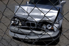 Car Wreck Smashed Hood and Grill with Headlights Behind Fence Royalty Free Stock Photo