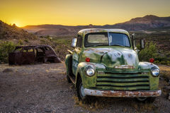 Car wrecks in the Mojave desert on route 66. COOL SPRINGS, ARIZONA, USA - MAY 19, 2016: Car wrecks in the Mojave desert on historic route 66 at sunset Royalty Free Stock Photography