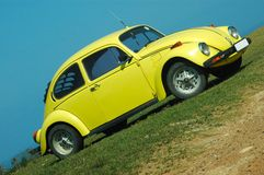 Car in yellow. A small yellow oldtimer car standing and parked on the lawn outdoors in front of blue sky Royalty Free Stock Photo