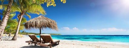 Caraïbisch Palm Beach met Houten Stoelen en Straw Umbrella royalty-vrije stock foto's
