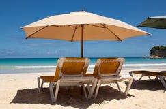 Caraïbische kleuren: sunbeds en paraplu's op openbaar strand, intense blauwe overzees en hemel: tropisch paradijs royalty-vrije stock afbeelding