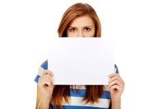 Cara adolescente de la cubierta de la mujer con la tarjeta en blanco Fotografía de archivo