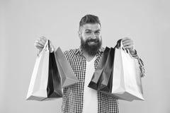 Cara alegre do moderno farpado do homem para levar os sacos de compras de papel no fundo amarelo Aprecie o preto rent?vel de comp foto de stock royalty free