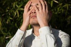 Cara aliviada de la cubierta del hombre joven con la mano mientras que coloca agains Imagen de archivo libre de regalías