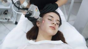 Cara ascendente cercana de la mujer joven en el procedimiento de peladura facial del laser, cámara lenta metrajes