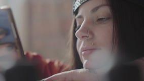 Cara ascendente cercana de una mujer joven con el labio y el anillo perforados en la nariz que manda un SMS en el teléfono móvil  almacen de metraje de vídeo