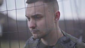 Cara ascendente próxima da posição do soldado em sua veste à prova de balas atrás da rede Um homem está no serviço militar E vídeos de arquivo