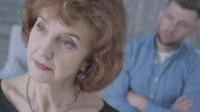 Cara ascendente pr?xima de uma mulher triste elegante madura superior que olha afastado no primeiro plano A figura borrada de um  vídeos de arquivo