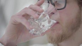 Cara ascendente próxima do homem pensativo farpado louro na água potável dos vidros do fim de vidro acima Homem de neg?cios consi vídeos de arquivo