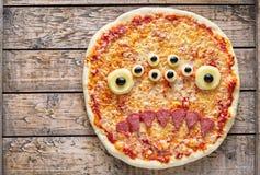 Cara asustadiza creativa del zombi del monstruo de la comida de Halloween con bocado de la pizza de los ojos imagen de archivo libre de regalías