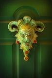 Cara asustadiza en una puerta verde Imagenes de archivo