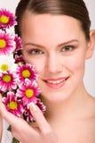 Cara atractiva de la mujer joven con las flores Imagen de archivo