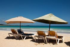 Cara?bische kleuren: sunbeds en paraplu's op openbaar strand, intense blauwe overzees en hemel: tropisch paradijs stock foto