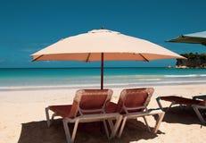 Cara?bische kleuren: sunbeds en paraplu's op openbaar strand, intense blauwe overzees en hemel: tropisch paradijs stock fotografie
