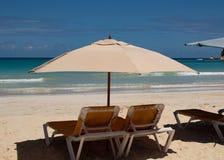 Cara?bische kleuren: sunbeds en paraplu's op openbaar strand, intense blauwe overzees en hemel: tropisch paradijs stock foto's