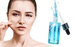 Cara bonita da jovem mulher perto da garrafa cosmética azul imagens de stock