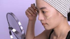 A cara bonita da mulher asiática compõe pelo líquido da fundação imagem de stock