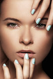 A cara bonita da mulher com azul prega o tratamento de mãos, pele limpa Foto de Stock
