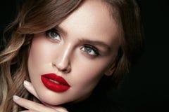 Cara bonita da mulher com composição e os bordos vermelhos imagem de stock