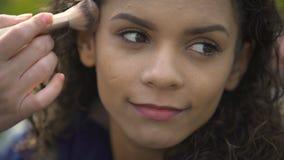 Cara bonita de la actriz de sexo femenino sonriente hermosa, artista de maquillaje que aplica el polvo metrajes