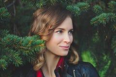 A cara bonita de uma jovem mulher de sorriso contra um fundo do abeto ramifica Imagens de Stock