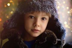 Cara bonita, sorrindo de um rapaz pequeno em um tampão da pele do inverno Olhos grandes fotos de stock royalty free