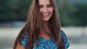 Cara bronceada de una chica joven encantadora con el pelo largo, que sensual presenta en la cámara por la tarde en la costa almacen de metraje de vídeo