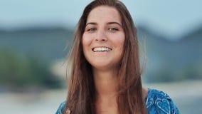 Cara bronceada de una chica joven encantadora con el pelo largo, que sensual presenta en la cámara por la tarde en la costa almacen de video
