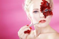 Cara con plumas rojas y un cepillo del labio Imagen de archivo libre de regalías