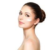 Cara da beleza da mulher com creme cosmético na cara foto de stock