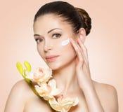 Cara da beleza da mulher com creme cosmético na cara imagem de stock