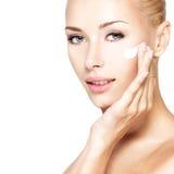 Cara da beleza da mulher que aplica o creme cosmético na cara Imagens de Stock Royalty Free