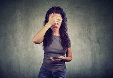 Cara da coberta da mulher no desespero que tem más notícias no smartphone contra o fundo cinzento foto de stock royalty free