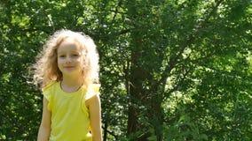 Cara da criança fora fêmea com sorriso encantador na luz solar no parque durante horas de verão A menina está enviando o ar vídeos de arquivo