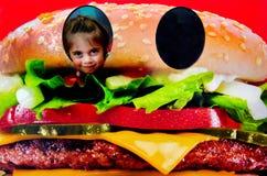 Cara da criança pequena dentro de um Hamburger Fotos de Stock Royalty Free