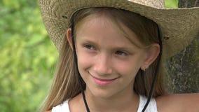Cara da criança que olha in camera de sorriso, fazendeiro Girl Portrait Outdoor na natureza 4K video estoque