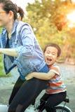 Cara da felicidade das crianças asiáticas que jogam na bicicleta com a mãe para o relacionamento de famílias imagem de stock