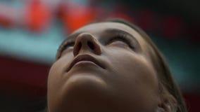 Cara da jovem mulher que que olha acima aos telhados da janela video estoque