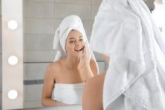 Cara da lavagem da jovem mulher com sabão perto do espelho imagens de stock royalty free