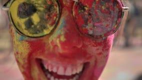 A cara da menina feliz nova no pó colorido com óculos de sol está sorrindo no festival do holi no dia no verão, cor filme