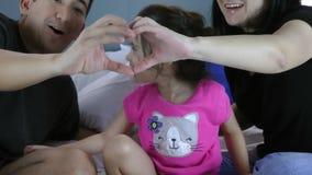 Cara da menina nas mãos da mãe e do pai, coração-dadas forma O símbolo do cuidado, a educação e a família amam vídeos de arquivo