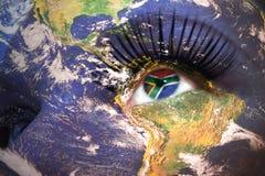 A cara da mulher com textura da terra do planeta e a bandeira de África do Sul dentro do olho Imagem de Stock Royalty Free
