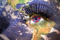 A cara da mulher com textura da terra do planeta e a marinha do confederado levantam a bandeira dentro do olho fotografia de stock royalty free