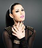 A cara da mulher da forma com pregos pretos e brilhantes bonitos fazem Fotografia de Stock