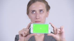 Cara da mulher de negócios loura nova feliz que pensa ao mostrar o telefone vídeos de arquivo